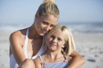 Портрет улыбающейся молодой женщины, улыбающейся и дочери, отдыхающей на песчаном пляже — стоковое фото