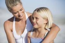 Крупный план молодой женщины, улыбающейся с дочерью на пляже — стоковое фото