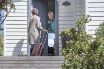 Uomo anziano benvenuto donna alla porta — Foto stock
