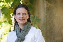 Портрет вдумчивой зрелой женщины с шарфом, смотрящей на улицу — стоковое фото
