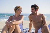 Couple romantique assis sur la plage et se regardant — Photo de stock