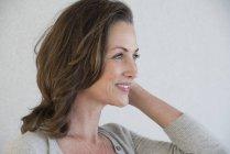 Усміхаючись зріла жінка, стоячи на сірий фон — стокове фото