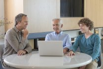 Happy senior man with son and grandson sitting at table with laptop in living room — Stock Photo