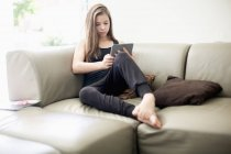 Teenage girl using digital tablet on couch at home — Stock Photo