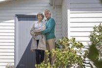 Retrato de feliz casal sênior abraçando fora de casa — Fotografia de Stock