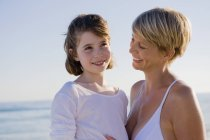 Donna con figlia che si gode le vacanze sulla spiaggia — Foto stock