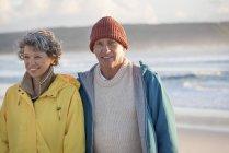 Happy senior couple standing on beach at sunset — Stock Photo
