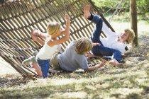 Маленькі діти падають з гамака в літньому саду — стокове фото