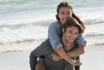 Happy young woman riding piggyback on boyfriend shoulders on beach — Stock Photo
