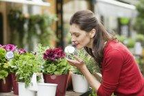 Elegante Frau, die im Blumenladen im Freien Blumen riecht — Stockfoto
