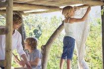 Children playing in tree house in summer garden — Stock Photo
