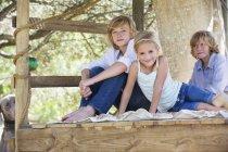 Retrato de crianças sentadas na casa da árvore no jardim de verão — Fotografia de Stock