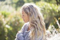 Donna che indossa maglione accogliente in piedi in giardino — Foto stock