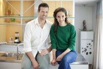 Couple assis sur le comptoir de la cuisine et souriant — Photo de stock