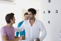 Men greeting each other in modern apartment — Stock Photo