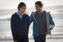 Счастливая романтическая молодая пара прогуливаясь по пляжу — стоковое фото