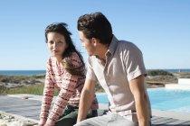 Pareja romántica sentada en el paseo marítimo en la playa - foto de stock