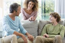 Happy family talking in living room at home — Stock Photo