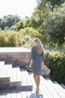 Блондинка в платье наслаждается в деревянной лестнице в саду — стоковое фото