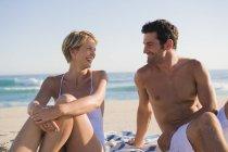 Couple souriant romantique assis sur la plage et se regardant — Photo de stock