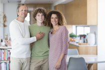 Portrait of happy family smiling while standing at home together — Stock Photo