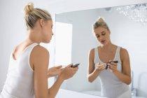 Mujer joven rubia aplicar Crema hidratante en la cara en el baño - foto de stock
