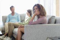 Gelangweilte Frau sitzt auf Sofa im Wohnzimmer mit Mann und Sohn im Hintergrund — Stockfoto
