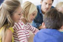 Крупный план родителей с детьми, сидящими дома вместе — стоковое фото