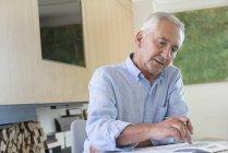 Старший использует калькулятор во время бумажной работы дома — стоковое фото