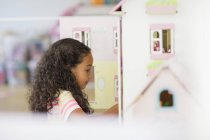 Menina brincando com casa de bonecas no quarto — Fotografia de Stock