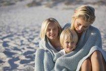 Портрет улыбающейся матери и детей, завернутых в шаль, сидящих на пляже — стоковое фото