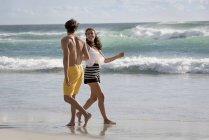 Счастливая веселая молодая пара, имеющая на летнем пляже — стоковое фото