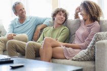 Happy family sitting on sofa and talking in living room at home — Stock Photo