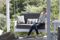 Happy woman relaxing on swing chair at porch — Stock Photo