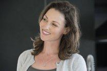 Sourire de femme d'âge mûr avec commandes de cheveux bruns sur fond foncé — Photo de stock