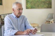 Homem sênior usando telefone celular ao fazer papelada em casa — Fotografia de Stock
