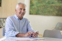 Retrato de homem idoso feliz usando telefone celular enquanto fazendo papelada em casa — Fotografia de Stock