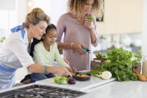 Senior woman with daughter and granddaughter preparing food in kitchen — Stock Photo