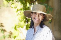 Portrait of senior woman wearing straw hat and smiling in garden — Stock Photo
