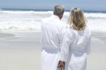 Вид сзади пары в халатах, стоящей на пляже и смотрящей на вид — стоковое фото