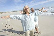 Couple avec les bras tendus et les yeux fermés relaxant sur la plage — Photo de stock