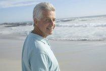 Портрет улыбающегося человека на песчаном пляже — стоковое фото