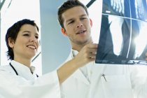 Close-up of two doctors examining X-Ray report — Stock Photo