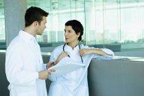 Ärzte diskutieren Krankenakte in Klinik — Stockfoto