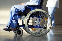 Низький розділ вид пацієнта сидячи в інвалідному візку з лікарем на тлі — стокове фото