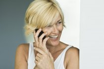 Laughing mature woman talking on mobile phone — Stock Photo