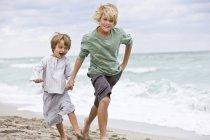 Веселые мальчики бегают по песчаному пляжу — стоковое фото