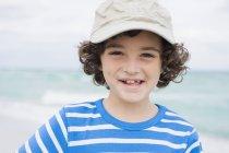 Портрет улыбающегося мальчика в кепке на пляже — стоковое фото
