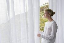 Mujer joven y serena de pie en el balcón y mirando a la vista - foto de stock