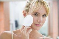 Jovem mulher aplicando pó facial com bola de algodão — Fotografia de Stock